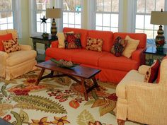 Helen Richardson designed this country living room with bold patterns set against a bright orange couch. Vibrant hues and dark wood furnishings emit visual warmth while pale yellow walls tone down the bold sofa and reflect the softer shades visible in the area rug's floral design. Rustic decorative stars pull in the country feel in a simple and subtle way.