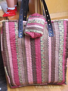 This look like it is made with strips from cut-down jelly rolls with embroidered quilting; I used the same technique to make a pair of cushions with a batik jelly roll, though did not narrow the strips.
