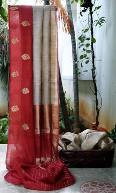 Light grey tussar with thin gold stripes along the length of the body. The saree has a wide maroon border which flows into the pallu. Pinned by Sujayita