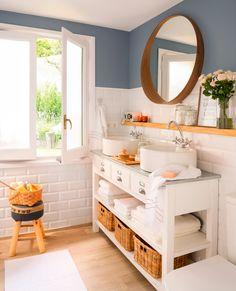 Baño con lavamanos con cajones y estantes y espejo redondo
