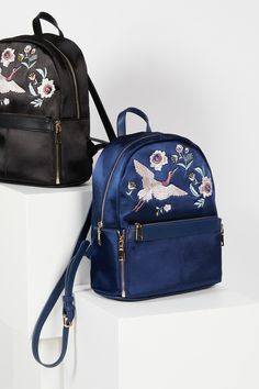 Magic Gardens Satin Backpack | Silky satin backpack featuring beautiful embroidery detailing. *Front pocket can be zippered off and used as a clutch. * Zip top closures * Lined interior with zip and slip pockets * Adjustable vegan leather straps