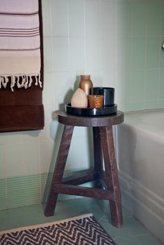 bathroom // the painted stool next to tub with a small tray for candles and bubble bath