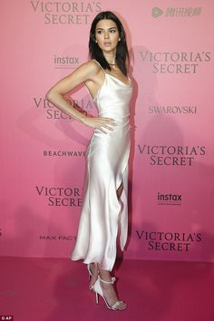 A vision in white: Kendall Jenner celebrated the honour in style as she sported a slinky white slip dress as she arrived in the press room at the Grand Palais in Paris after the style bonanza