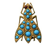 An early 1900s brooch in the form of a fly, studded with turquoise glass beads, and red glass eyes. In gilt metal.  From Erie Basin Antiques.