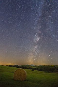 Meteor In a Haystack.  A view of the Milky Way rising above a farm and a bale of hay in rural Loudon County, Virginia near Delaplane, with a meteor streaking towards Earth.  Astrophotography by Andrew Rhodes.