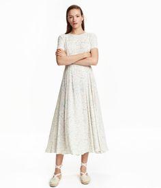 Lang kjole i tynd viskose med trykt mønster. Kjolen har korte ærmer og åbning med trykknapper i nakken. Skåret i taljen med smalt bindebånd. Klokkeformet underdel. Uden for.