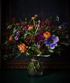 Rosehips, Anemones and orange Ranunculous by Scarlet & Violet, London England