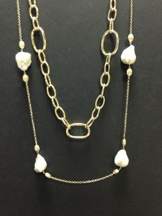 Yellow gold link necklace layered with yellow gold and baroque pearl necklace. Available at www.yanina-co.com, 800-780-3433.
