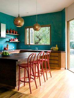 une cuisine éclectique dynamisée par la couleur canard sur les murs et par la déco aux nuances de terre de sienne