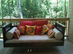 deep brown bed swing with high arm rest and many pillows