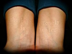 """The heart is a lonely hunter"" white ink tattoo."