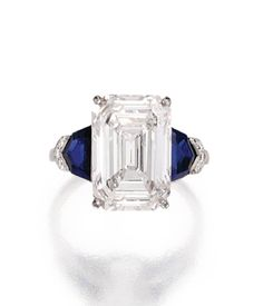 Platinum, diamond and sapphire ring | Raymond Yard. Centered by an emerald-cut diamond weighing 6.23 carats, flanked by two shield-shaped sapphires and six single-cut diamonds, size 6, signed Yard.