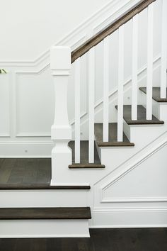 Curved custom newel post The staircase features curved custom newel post, wainscoting and dark stained stair treads #curvednewelpost