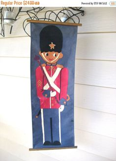 This vintage Christmas wall hanging depicts a smiling toy soldier in a red uniform. This is a long fabric banner with a string for hanging on