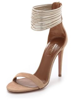 Spin me around sandals by Aquazzura. Skinny metallic strands form a wide ankle cuff on these suede Aquazzura sandals. Tonal back zip. Covered stiletto hee...