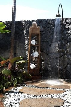Love the outdoor shower Plants and rocks, towel rack