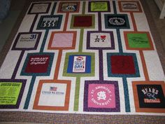 """Eighteen t-shirts were cut down into 12"""" squares to make this quilt. 5 tonal fabrics were used and a multi-pattern with all of the colors w..."""