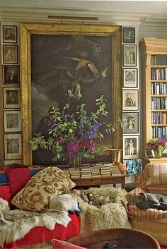Robin Birley's London bedroom - love the large painting with the smaller ones around it and the pile of books!!