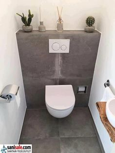 Toilet room with ceramic tiles in concrete look and fountain with wooden washbas. Toilet room with