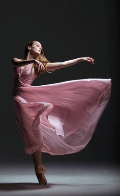 Ballerina dancing point in beautiful pink dress, graceful beauty.