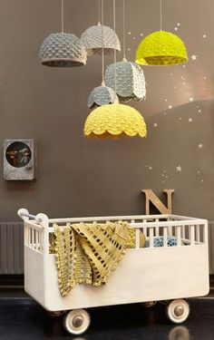 Cool wheels on crib and neat lamp shade mobile