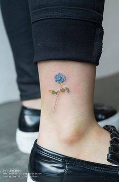 Small blue rose tattoo on the ankle.