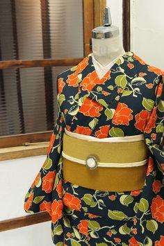 濃紺色の地に、山茶花のような椿のような花模様が染め出されたウールの単着物です。