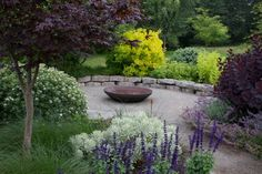 A rusting steel fire pit, surrounded by a basalt stone seating wall.  See more at mosaic-gardens.com.