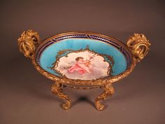 An absolutely gorgeous Sevres porcelain bowl with gilt bronze mounts, four figural legs (they appear to be rams) and two handles decorated with a floral motif. It is hand painted with a putti angel and gilt. The image of the cherub is sitting on a cloud and surrounded by a rich turquoise color and a deep navy blue border. The mark underneath indicates the artist was Denis Lev who was active 1754-1793 and 1795-1805.