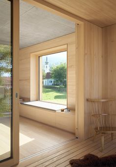 Blonde wood interior (floors and paneling) contrasts with the blackened timber exterior in this Austrian home. Show here: a cozy window reading nook.