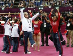US gymnast Gabrielle Douglas (R) and coach John Geddert celebrate with the rest of the team after the Americans won gold in the women's team of the artistic gymnastics event on July 31, 2012.