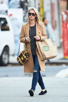 Nicky Hilton brings a downtown vibe to her pristine camel coat with ripped up skinny jeans and a fun Louis Vuitton bag.