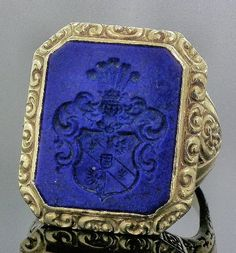 A gentleman's gold coloured metal signet ring inset with oblong lapis lazuli panel engraved with crest within scrolling borders (gross weight 11 grammes - ring size P)