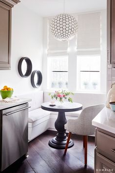 A dream realized in this new home for Foster was her kitchen breakfast nook, which the designers furnished with a custom corner banquette, a pedestal table from Crate & Barrel, and a capiz orb...