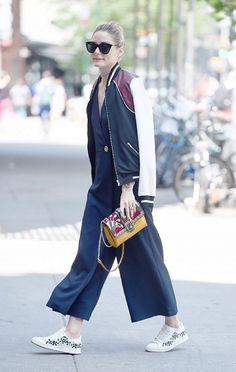 Olivia Palermo usa óculos modelo gatinho, macacão azul marinho, jaqueta bomber, bolsa com estampas e tênis branco