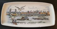 Holland America Cruises  Vintage Ash Tray , circa 1959  hand painted Port of Rotterdam with the ss Rotterdam in the background with Holland America Cruises old logo on bottom  made by Royal Goedewaagen Gouda Holland makers of Blue Delft Tile, artistic pottery, pipes, and more  measures 9 1/4'' lg x 4 1/2'' wd