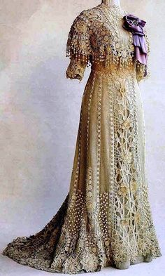 """Elegant lace tea gown, ca.1900, with a purple / grey ombre underdress. Thank you to Lynn Griffiths who was kind enough to provide the following information on this dress: This beautiful Irish crocheted dress was worn by Anna Vidal I Sola de Rocamora at the turn of the 20th Century. The photo comes from Annie Potter's book, """"A Living Mystery, the International Art & History of Crochet"""" and is courtesy of the Museo Textil y de Indumentaria, Spain."""