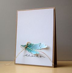handmade thank-you card from My Paper Secret ... clean and simple design ... kraft with white panel ... two die cut feathers painted in aqua and topped with sparkling glitter ... twine bow with very long ends holds them together ... great card!!