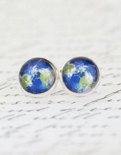 Delightful silver plated brass stud earrings boast a green and blue print of the earth from space. The earrings are covered with clear glass domes.