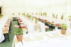 Wedding tables inside marquee with geraniums in pots