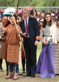 Prince William, Duke of Cambridge fires an arrow as Catherine, Duchess of Cambridge looks on during an Bhutanese archery demonstration on the first day of a two day visit to Bhutan on the 14th April 2016 in Paro, Bhutan.