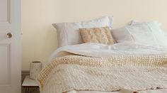 Pour donner de la douceur au blanc, optez pour les tons naturels. Les murs Poudre d'Ivoire et le linge de lit blanc associés à la douceur de la laine, du feutre et du coton donnent une ambiance cosy à cette chambre aussi lumineuse que chaleureuse.