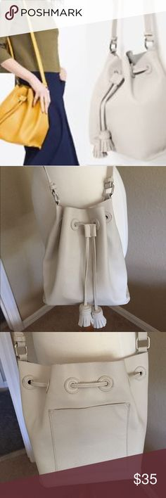 Zara Bucket Bag TRENDING!!! Classic Zara basics drawstring bucket bag. Gently used excellent condition. Color is off white/ winter white. Drawstring with tassels, adjustable strap, and large tech pocket on back of purse. See other listing with more pictures.       Nonsmoking ***   Measurements are from seam to seam.  GREAT PRICE!!!   No Trades plz😊😊 Zara Bags Shoulder Bags