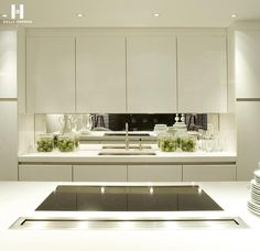 White countertop, white cabinets, mirrored backsplash