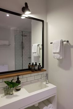Small wood shelf under mirror. HASSELL | Projects - Ovolo Laneways