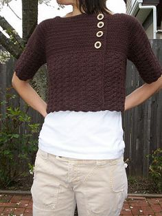 This cardigan is an easy top down project. The cardigan begins at the neck and is worked back and forth in half double crochet until reaching the underarms. On every row the yoke of the cardigan is increased along raglan lines. After the yoke is completed, the cardigan continues in a solid shell stitch pattern. This double breasted cropped cardigan is meant to be close-fitting with a slightly boxy shape, but it is easy to adjust both the sleeve and body length.