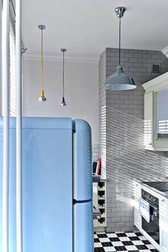 Wnętrze kuchni utrzymane w klimacie loftu. Ściana kominowa obłożona szarą glazurą w cegiełkę. Pozostałe ściany utrzymane w podobnej tonacji kolorystycznej. Na posadzce – klasyczna czarno-biała geometryczna mozaika. A na pierwszym planie bryła niebieskiej lodówki Smeg utrzymanej w klimacie retro.