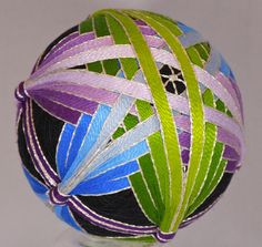 This is a Japanese ball that is wrapped w/ yarn and thread around material to make a mari base. Then the ball is divided and stitched w/ embroidery thread ...