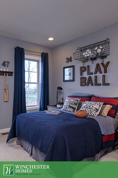 With floor-length blue curtains and red and navy bedding, this Newport model bedroom is the perfect backdrop for a sports bedroom theme. #InteriorDesign #DreamHome
