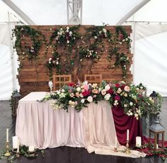 12 a wooden backdrop with greenery and lush blooms and matching ones on the table - Weddingomania